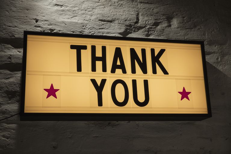 Close-up-of-thank-you-signboard-against-gray-wall-691036021-5b0828a843a1030036355fcf