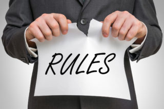 Businessman_tearing_rules_GettyImages-656916194-320x213